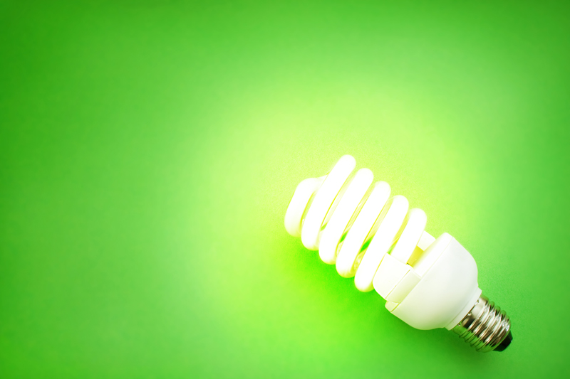 Energy saving lamp on absctract green background